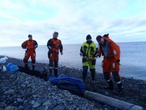 Nils, Ted og Tom Richard skifter om til kystvaktas overlevingsdrakter og er klar for hjemreise. Stasjonssjef Kåre bivåner det hele og transporterer dem ut til KV Svalbard.