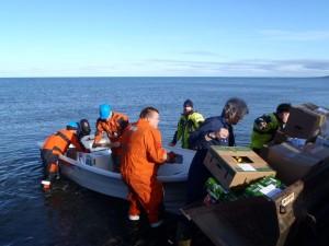 Alle tok del i utlemping av utstyr, bagasje og proviant fra lettbåten. Både gammelt og nytt mannskap sees i full aktivitet her.