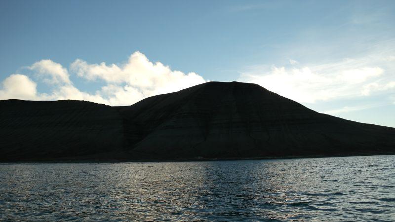 Johan Hjortfjellet sett fra sjøen på østsiden og med  motlys.