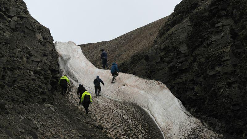 Besøkende klatrer opp snøfonna i bunnen av skaret.