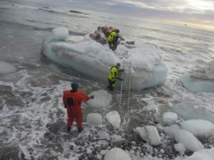 Så måtte varene bæres fra isflaket, gjennom sjø, issørpe og store isklumper til land og opp på landkalven. Foto: Tom Erik Glomsrud