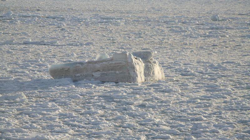 Her og der stikker større isflak og isklumper opp av isen.