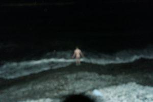 Menig Høgevold på vei ut i et frysende kaldt Barentshavet for ta testen som kreves for å bli medlem i den eksklusive klubben Hopen Nakenbaderforening, Bildet ble naturlig sladdet pga vanskelig fotoforhold i mørketida